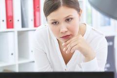 年轻亚裔女商人与膝上型计算机一起使用在办公室 库存图片