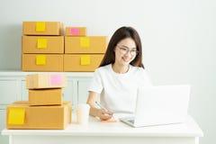 年轻亚裔女孩在家是有她的私人企业办公室的自由职业者,与膝上型计算机一起使用,咖啡,网上营销,顾客o 免版税库存照片