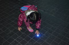 年轻亚裔女孩好奇对在地板的光 免版税库存照片
