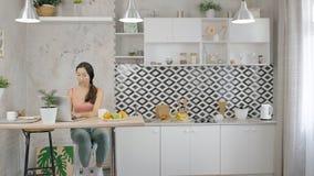 年轻亚裔女性在坐在桌上的膝上型计算机键入在现代厨房里 影视素材