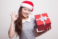 年轻亚裔妇女以圣诞老人帽子与礼物盒的展示OK 图库摄影