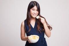 年轻亚裔妇女吃土豆片 库存图片