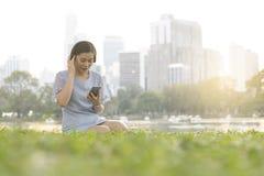 年轻亚裔妇女听到音乐通过佩带无线耳机和采取智能手机 库存照片