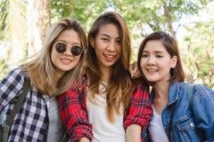 年轻亚裔妇女坐沿街道享受他们的城市生活方式的小组在一个早晨 免版税库存照片