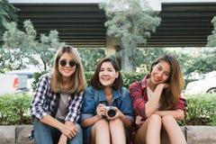 年轻亚裔妇女坐沿街道享受他们的城市生活方式的小组在周末等待的一个早晨室外 免版税库存图片