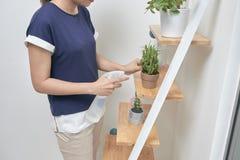 年轻亚裔妇女培养水到植物 免版税库存照片