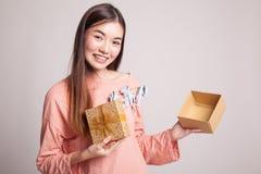 年轻亚裔妇女打开一个金黄礼物盒 库存图片