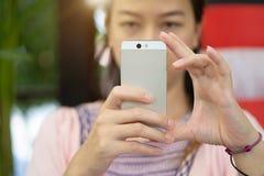年轻亚裔妇女的焦点手拍与智能手机的照片 免版税图库摄影