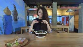 年轻亚裔妇女采取照片薄煎饼在咖啡馆 技术和人脉概念 股票视频