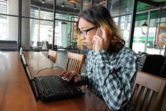 年轻亚裔工作者广角射击与膝上型计算机和巧妙的电话一起使用在办公室 库存图片