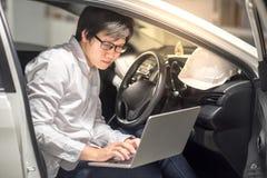 年轻亚裔工程师或建筑师与在他的汽车的膝上型计算机一起使用 库存图片