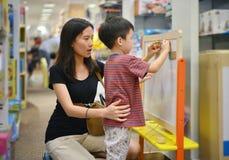 年轻亚裔母亲和她的孩子购物在商城戏弄 库存照片