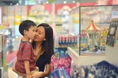 年轻亚裔母亲和她的孩子购物在商城戏弄 免版税库存照片