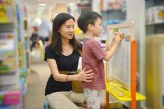 年轻亚裔母亲和她的孩子购物在商城戏弄 库存图片
