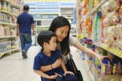年轻亚裔母亲和她的孩子购物在有迷离的超级市场 免版税库存照片