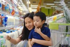 年轻亚裔母亲和她的孩子购物在有迷离的超级市场 免版税库存图片