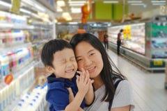 年轻亚裔母亲和她的孩子购物在有迷离的超级市场 库存照片