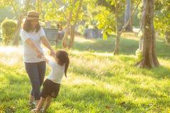 年轻亚裔母亲和小女儿播放有乐趣的公园和幸福,家庭一起享用和放松和休闲 免版税库存照片
