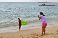 年轻亚裔母亲在海洋拍她的女儿照片  免版税库存图片