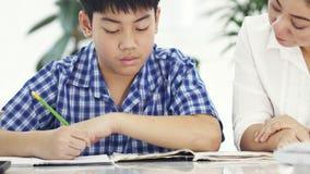 年轻亚裔母亲教学儿子在家 有做在桌上的儿子的亚裔母亲家庭作业与微笑面孔 移动式摄影车射击4K 影视素材