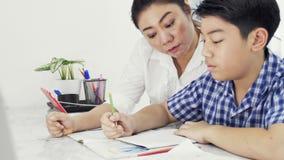 年轻亚裔母亲教学儿子在家 有做在桌上的儿子的亚裔母亲家庭作业与微笑面孔 移动式摄影车射击4K 股票录像