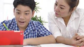 年轻亚裔母亲教学儿子在家 有做在桌上的儿子的亚裔母亲家庭作业与微笑面孔 移动式摄影车射击4K 股票视频