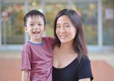 年轻亚裔母亲画象和她的孩子是愉快的 库存图片