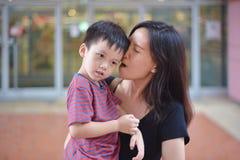 年轻亚裔母亲画象和她的孩子是愉快的 免版税库存照片