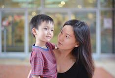 年轻亚裔看彼此的母亲和她的孩子 库存照片