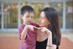 年轻亚裔看彼此的母亲和她的孩子 免版税库存照片