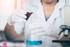 年轻亚裔科学家是在实验科学的某些活动象开发医学的混合的化学制品或词条数据, 免版税库存图片
