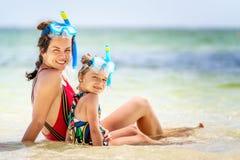 年轻享用海滩的母亲和小女儿在多米尼加共和国 免版税库存照片