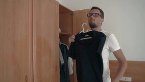 年轻亭亭玉立的人选择在早晨时间的T恤杉在他的公寓 股票录像