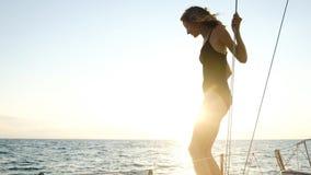 年轻亭亭玉立的女孩准备从一条航行的游艇跳进日落的公海 图库摄影