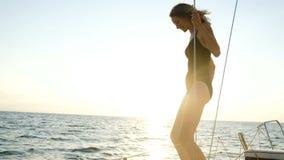 年轻亭亭玉立的女孩准备从一条航行的游艇跳进日落的公海 影视素材