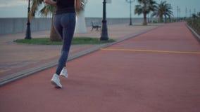 年轻亭亭玉立的女运动员在特别道路的晚上,后面看法单独跑步 股票录像