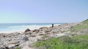 年轻亭亭玉立的嬉戏人跑一串岩石足迹 击中海洋的强的波浪 t 股票录像