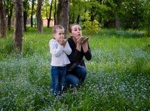 年轻亭亭玉立的母亲和五岁的女儿送一个亲吻 库存照片