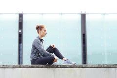 年轻人、适合和运动的女孩坐一个具体边界 健身,体育,都市跑步和健康生活方式概念 免版税库存照片