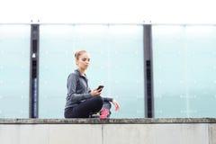 年轻人、适合和运动的女孩坐一个具体边界 健身,体育,都市跑步和健康生活方式概念 库存图片
