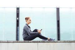 年轻人、适合和运动的妇女坐一个具体边界 健身,体育,都市跑步和健康生活方式概念 库存照片