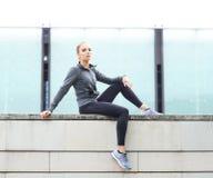 年轻人、适合和运动的妇女坐一个具体边界 健身,体育,都市跑步和健康生活方式概念 免版税库存照片