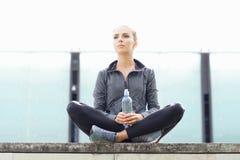 年轻人、适合和运动的妇女坐一个具体边界 健身,体育,都市跑步和健康生活方式概念 库存图片