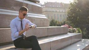 年轻人与他的smartwatch一起使用 股票视频