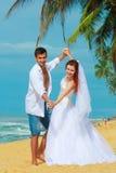 年轻人与在一个海滩的夫妇跳舞结婚在一个热带目的地 图库摄影