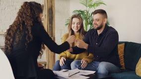 年轻人与房地产经纪人,签署的文件谈话并且采取房子钥匙,扣紧有地产商的手然后亲吻 股票录像