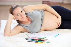 年轻人与铅笔的相当孕妇图画 免版税库存照片