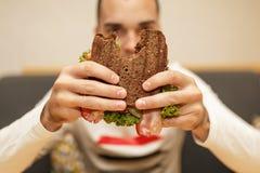 年轻人举行被咬住的三明治滑稽的被弄脏的protrait的关闭由他的两只手的 三明治在焦点 r 免版税库存照片