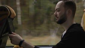 年轻人乘坐公共汽车并且看在位子垫头之物的显示器  股票视频