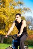 年轻人乘驾一辆自行车在秋天公园 免版税库存图片